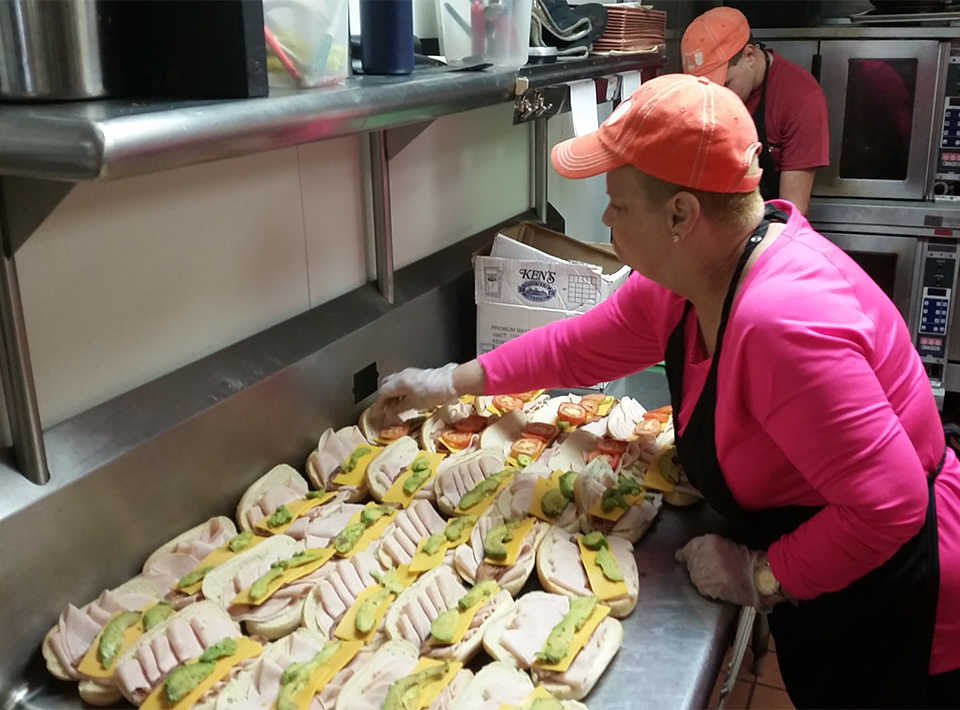 Civitan Foundation member works in kitchen preparing sandwiches.