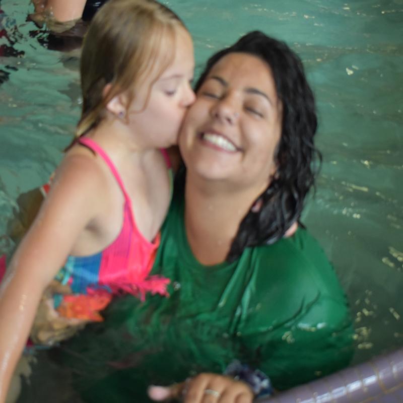Camp staffer being kissed on cheek in pool by camper.