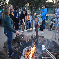 Campers and Staff roasting marsh mellows at fire.