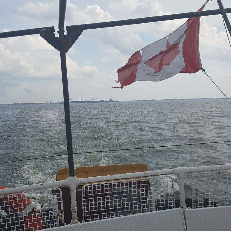 Photo of Canadian flag blowing in wind off aft of boat.